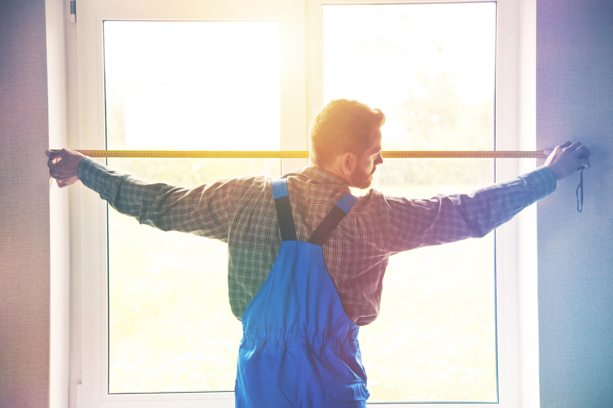 Service man installing window with measuring tape | High Demand Trade Jobs Include Window Repair and Replacement | Window Makeover