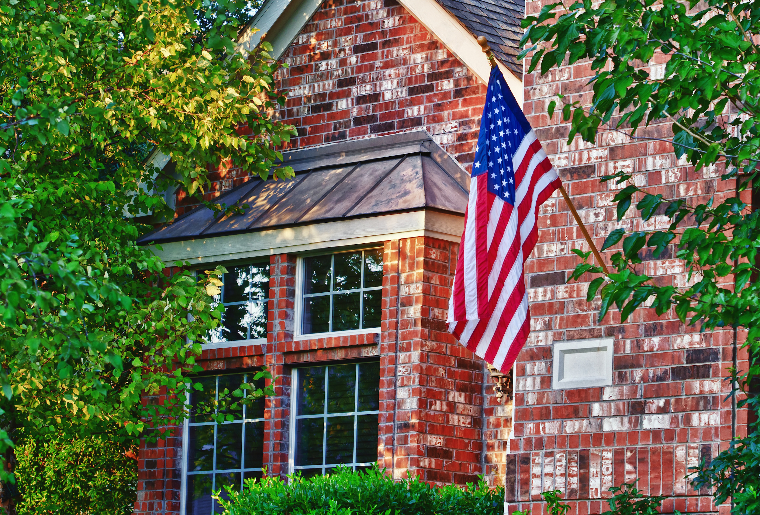 American flag in front of windows in red brick home | Best Glass Options for your Southern Atlanta Home Window Repair | Window Makeover