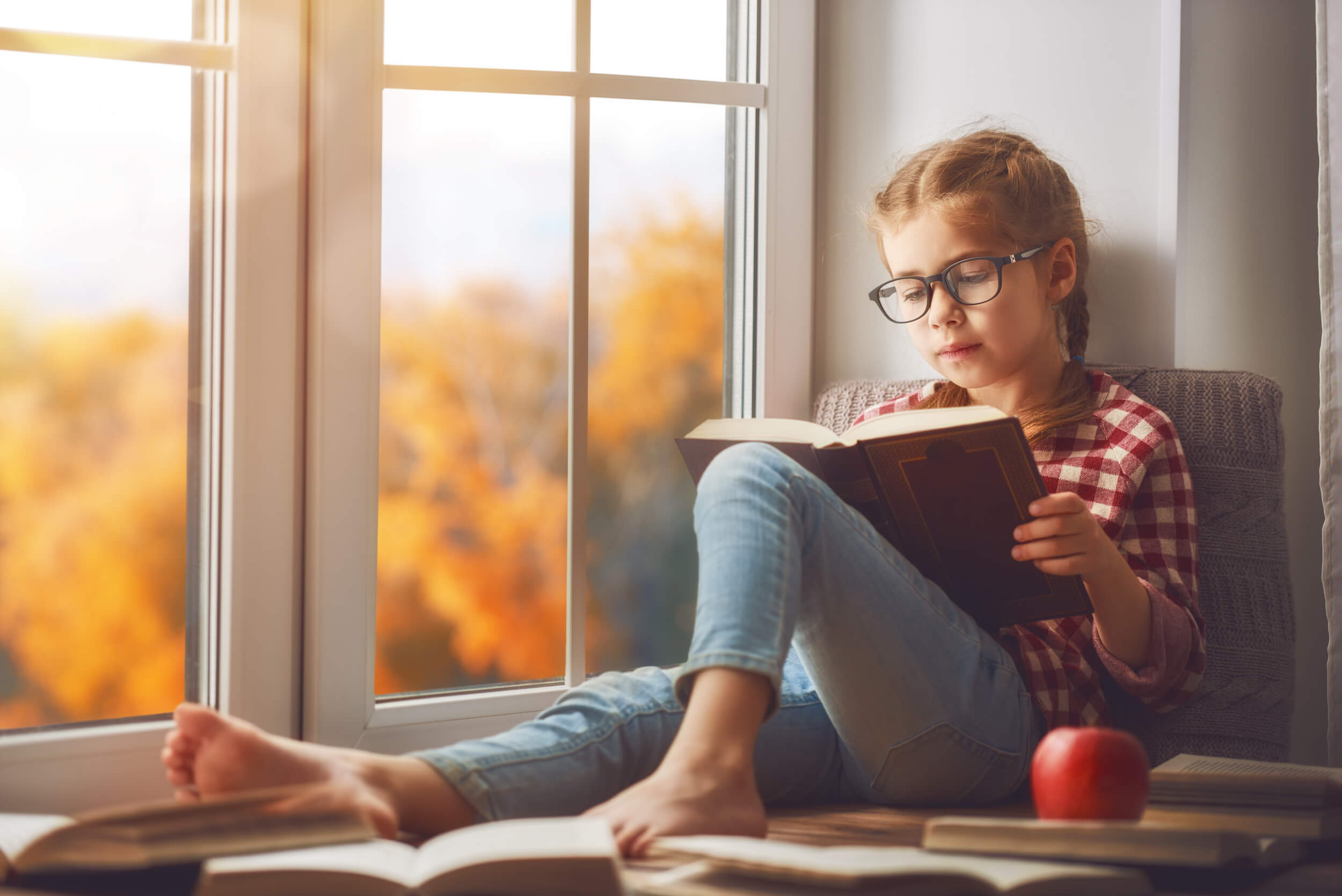 Young girl studying by windows with fall colors outside | Home Windows | Window Makeover