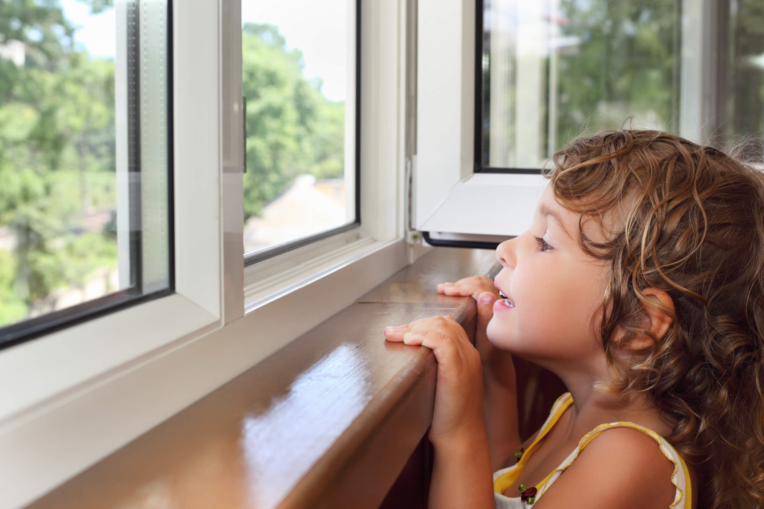 Young girl looking out the window | Window Repair | Window Makeover